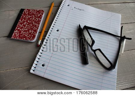 a notebook glasses pen pencil budget wooden background