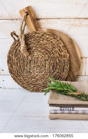 Wood round cutting board rattan coaster stack of linen kitchen towels rosemary twigs on white plank wood background Provence style kinfolk
