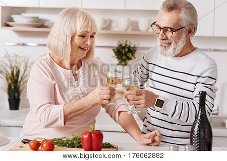Minutes of real happiness . Positive happy senior partners standing in the kitchen and cooking dinner while expressing love and drinking champagne