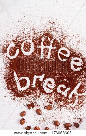 coffee break text made in ground coffee and coffee beans close up