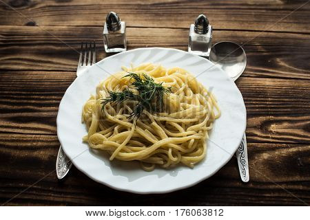 a plate with spagetti salt pepper woden background