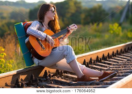 Hippie style Female Busker playing Guitar sitting on Railroad holding Backpack green Meadow and Forest on Background