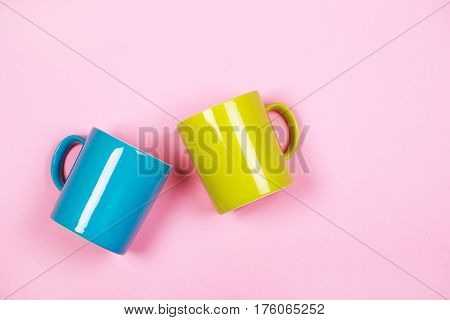 Two cups: greenery and blue on pink background. Flat lay.