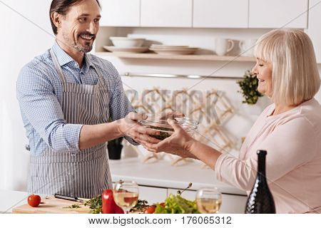 Full of positivity. Positive happy bearded man standing in the kitchen and enjoying weekend while cooking salad with his senior mother