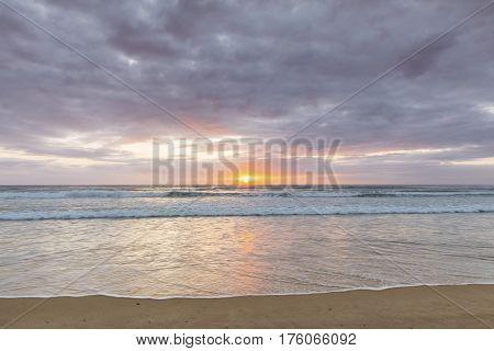 Gold Coast Surfers Paradise beach, ocean waves on a cloudy morning sunrise