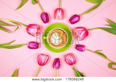 Tulips and greenery coffee cup with foam on pink background, top view.