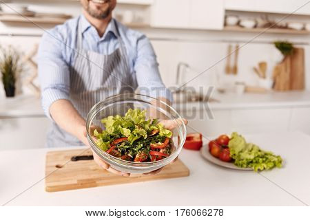 My enjoyable hobby. Skilled crafty positive man standing in the kitchen and holding the bowl full of salad while expressing positivity