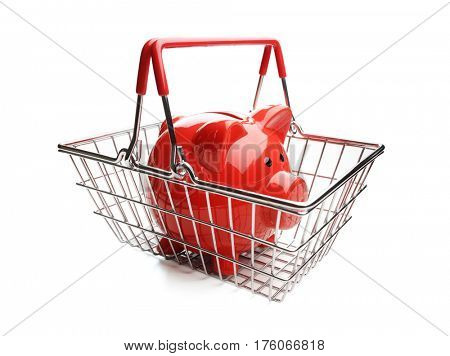Piggy bank in shopping basket on white background concept for cost of grocery shopping