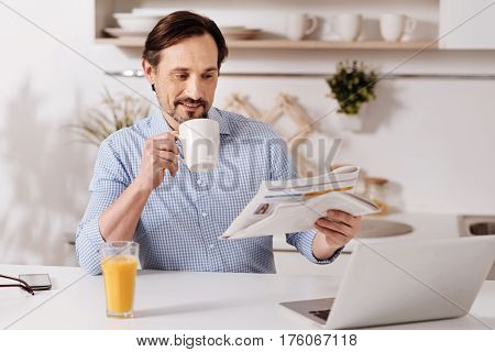 Relaxing and working at the same time. Satisfied intelligent involved businessman sitting at home and drinking cup of tea while using laptop and reading magazine