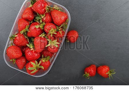 Strawberries in plastic box on a slate board.Horizontal photo food on natural background with text area for design menu cafe cooking recipe book.