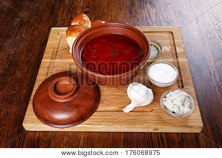 On the table is a plate of the Ukrainian borsch biscuits gravy boat with sour cream bacon milled and garlic sauce. top view