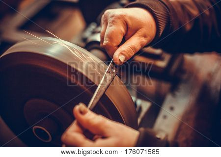 Close up shot of a man's hands sharpening a scissors.
