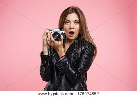 Closeup portrait of beautiful girl in fashion black leather jacket looking overwhelmed, holding old camera