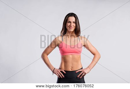 Attractive young fitness woman in sports bra and black leggings, slim waist, perfect fit female body, arms on hips. Studio shot on gray background.