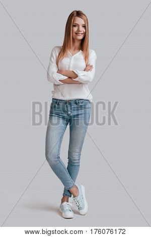 Confident woman. Full length of beautiful young woman in casual wear keeping arms crossed and looking at camera with smile while standing against grey background