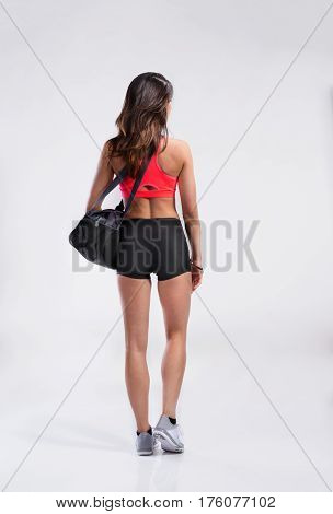 Attractive young fitness woman in orange sports bra and black shorts, carrying sports bag. Slim waist, perfect fit female body. Rear view. Studio shot on gray background.