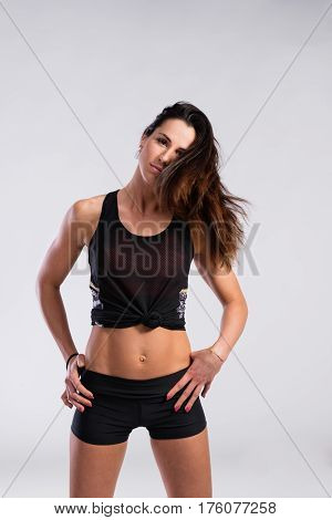 Attractive young fitness woman in black tank top and black shorts, flipping her hair, arms on hips. Slim waist, perfect fit female body. Studio shot on gray background.