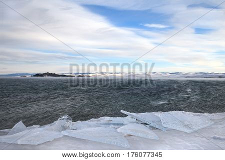 Transparent ice floes at frozen coast of stormy lake in winter