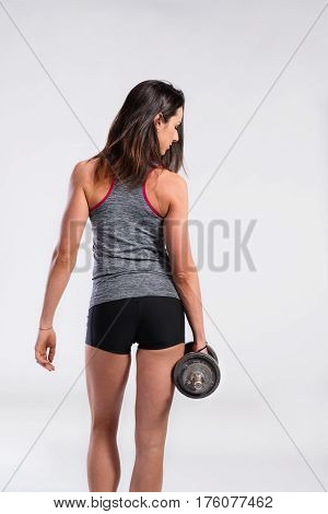 Attractive young fitness woman in tank top and black shorts, holding dumbbell. Slim waist, perfect fit female body. Rear view. Studio shot on gray background.