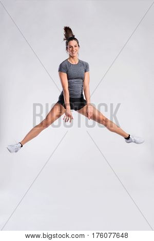 Attractive young fit woman in gray t-shirt and black shorts exercising fitness jumping. Slim waist, perfect fit female body. Copy space. Studio shot on gray background.