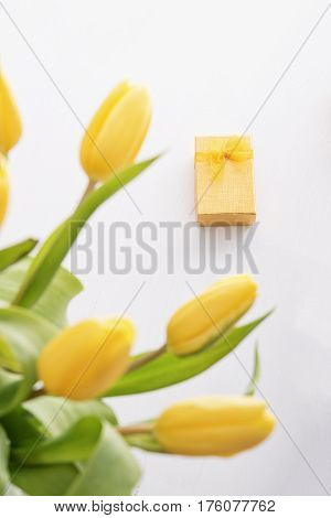 Fresh yellow tulips and golden gift box on white wooden table