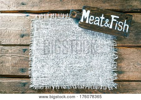 Vertical frame of white burlap on rough pine wood boards. Wooden tablet with text 'Meat and Fish' as title bar. Structured natural style background