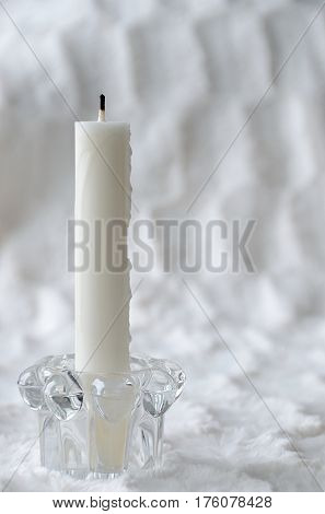 Flameless candle. White candle in candle holder made of glass against a white background.