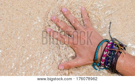 Women Hand with Colourful Wristband Toching Wet Sand on the Beach.