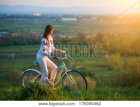 Woman With Retro Bike On The Hill In The Evening