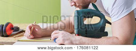 Carpenter Measuring Wood Plank