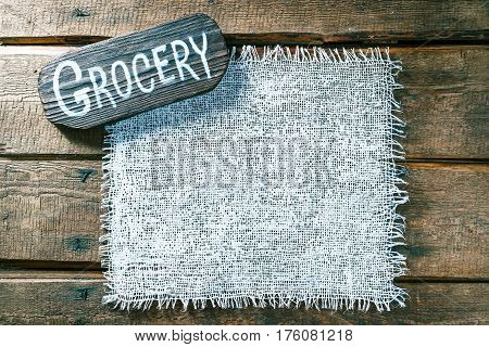 Vertical frame of white burlap on rough pine wood boards. Wooden tablet with text 'Grocery' as title bar. Structured natural style background
