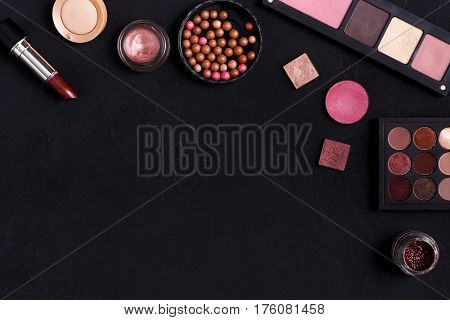 Makeup cosmetics and other essentials frame on black background. Top view, flat lay with copy space. Beauty tools palettes collection, lipstick, eyeshadow, ball blush, foundation and more