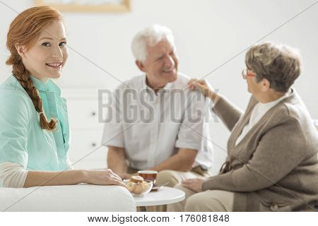 Young pretty nurse in a retirement house with her patients