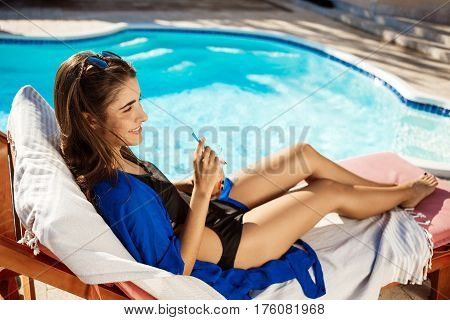 Beautiful brunette girl drinking cocktail, lying on chaise near swimming pool. Copy space.