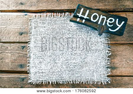 Vertical frame of white burlap on rough pine wood boards. Wooden tablet with text 'Honey' as title bar. Structured natural style background