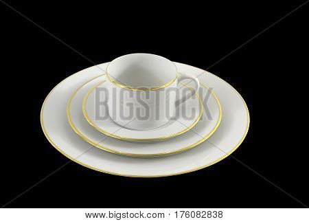 Set of white dinnerware with gold trim on a black background