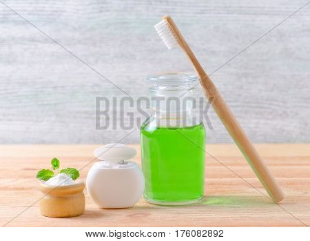 alternative natural mouthwash bottle with toothpaste xylitol or soda or salt and wood toothbrush dental floss on wooden background