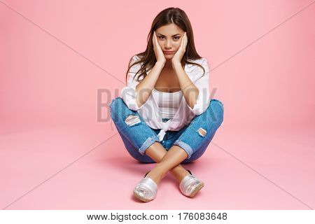Bored gril in fancy clothes sitting on floor with legs across, holding head looking straight