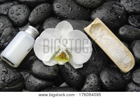 Beautiful orchid with salt in spoon, oil and wet stones background