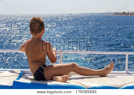 Tanned boy looking to the blue sea from yacht board in sunny day
