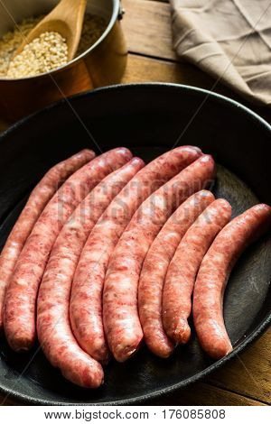 Raw uncooked pork and chicken sausages Spanish longaniza in iron cast pan kitchenware top view