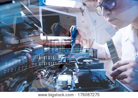 Throw the Window image of Computer Technician working with Hardware using tools in cold tones