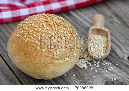 Bun with sesame seeds on wooden background