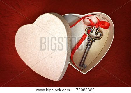 Valentines Day card: Key in heart shaped gift box on red grunge background