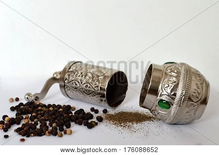 Pepper mill, peppercorn and grounded pepper on light background