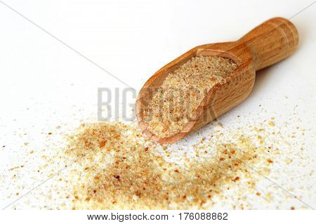 Breadcrumbs in wooden scoop on light background