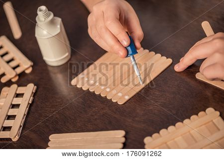 Close-up partial view of little girl handcrafting with ice cream sticks and glue