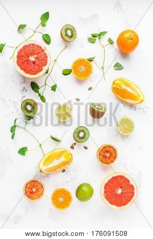 Colorful fresh fruit on white table. Orange tangerine lime kiwi grapefruit. Fruit background. Summer food concept. Flat lay top view