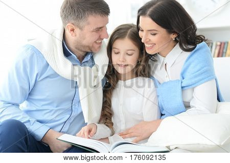 Portrait of a family with daughter reading a book