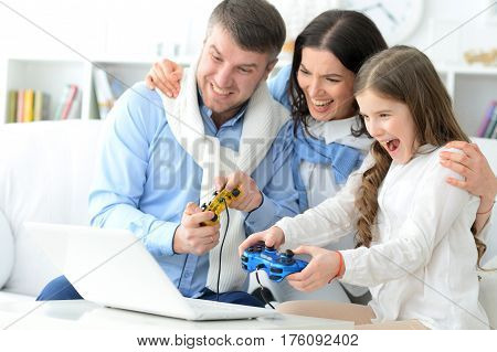 Family with daughter playing a computer game